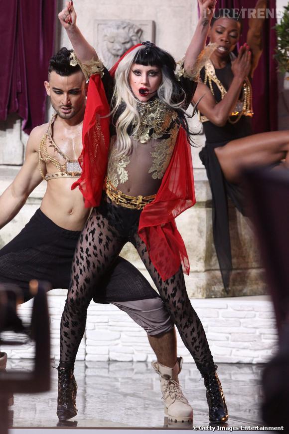 La chanteuse fait de chacune de ses apparitions un véritable spectacle mode comme ici avec un collant léopard Mugler et un body feuille d'or. Un long voile rouge vient parfaire cette allure théâtrale.