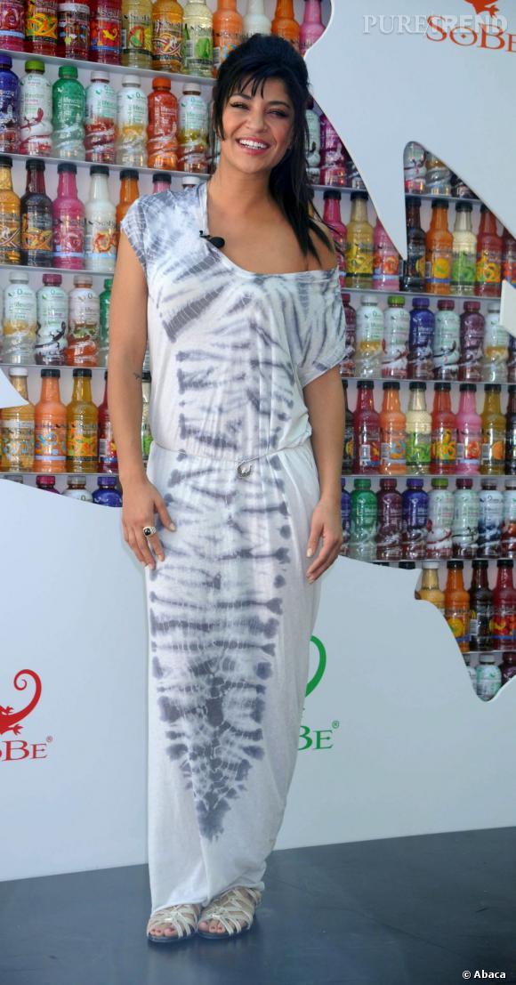 L'actrice mise sur une longue robe imprimée tie and dye flirtant avec le sol pour un look estival.