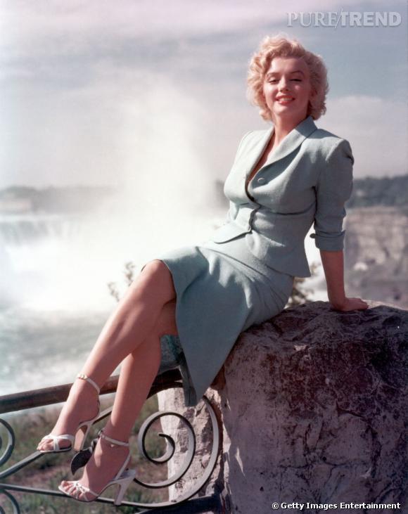 Dans un ensemble bleu pâle, veste et jupe au genou, la belle joue les working girl sexy.
