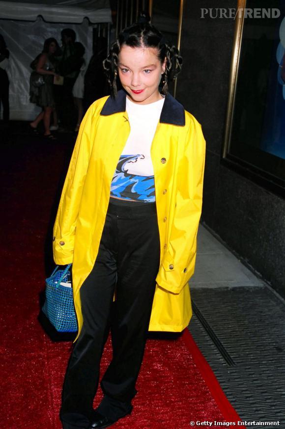 En trench jaune canari et pantalon taille haute, la chanteuse se perd dans les tendances et pousse l'excentricité des couleurs.