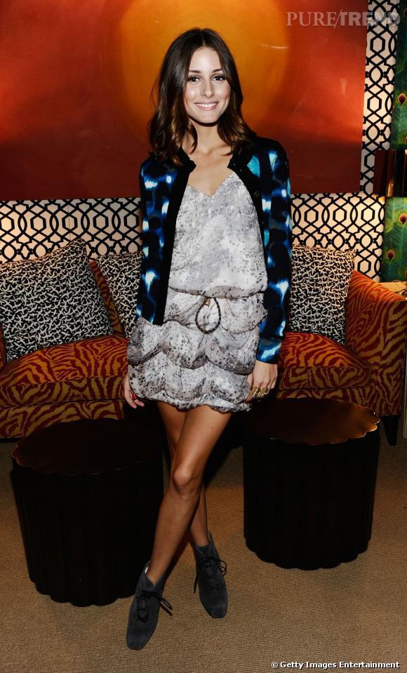 Bottines Proenza Schouler aux pieds et gilet coloré Diane Von Furstenberg, Olivia donne le ton. Elle craque pour une robe grise mettant en valeur sa carnation et marquée à la taille par une fine ceinture.