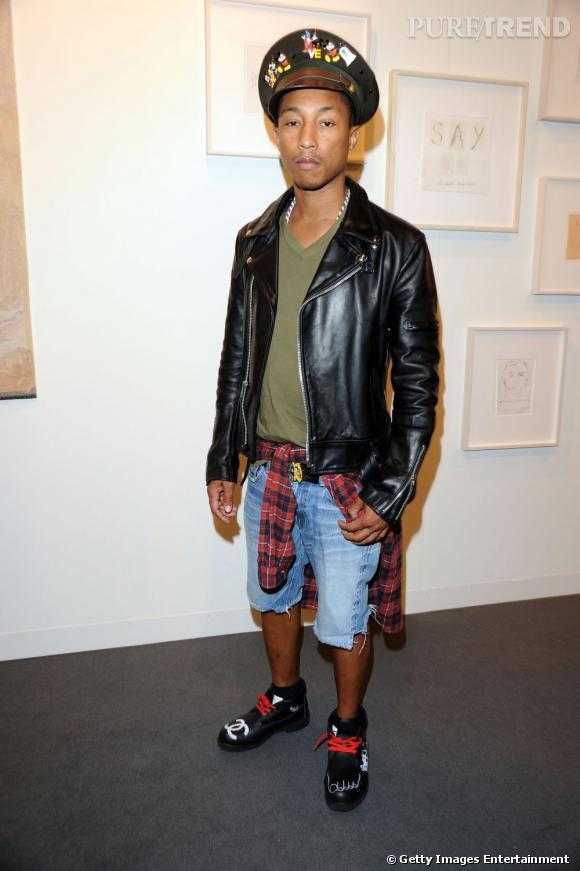Miami Art Basel   Pharell Williams en tenue d'attaque, casquette aux différentes décorations, perfecto noir et short en jean. A noter des chaussures siglées Chanel. L'homme de tous les croisements.