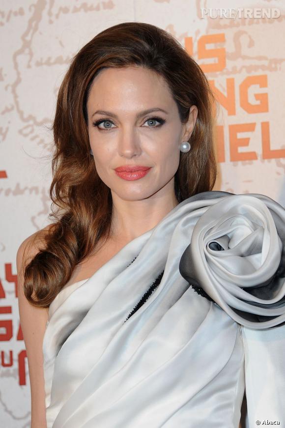 """En début d'année, pour présenter son film """"Au pays du sang et du miel"""" à Paris, Angelina Jolie choisit une coiffure one shoulder pour aller avec sa robe asymétrique."""