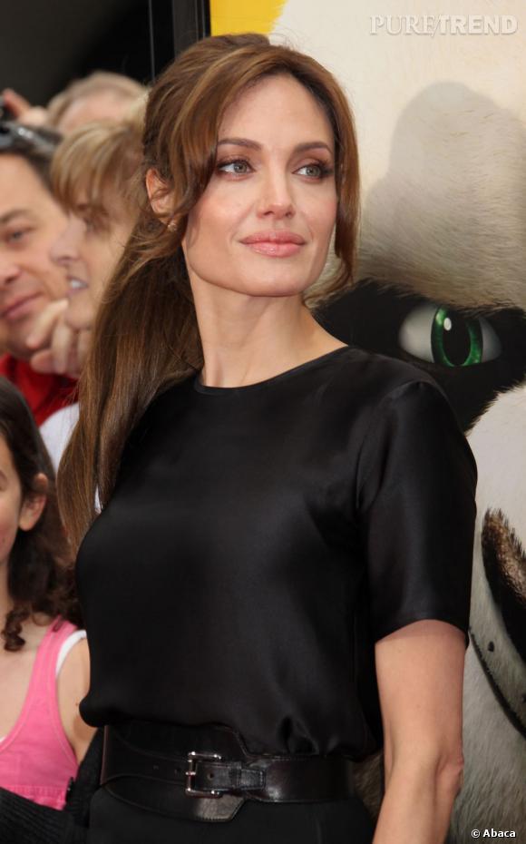Angelina Jolie remonte ses cheveux en demi-queue et laisse s'échapper deux mèches sur le devant. Simple et chic.