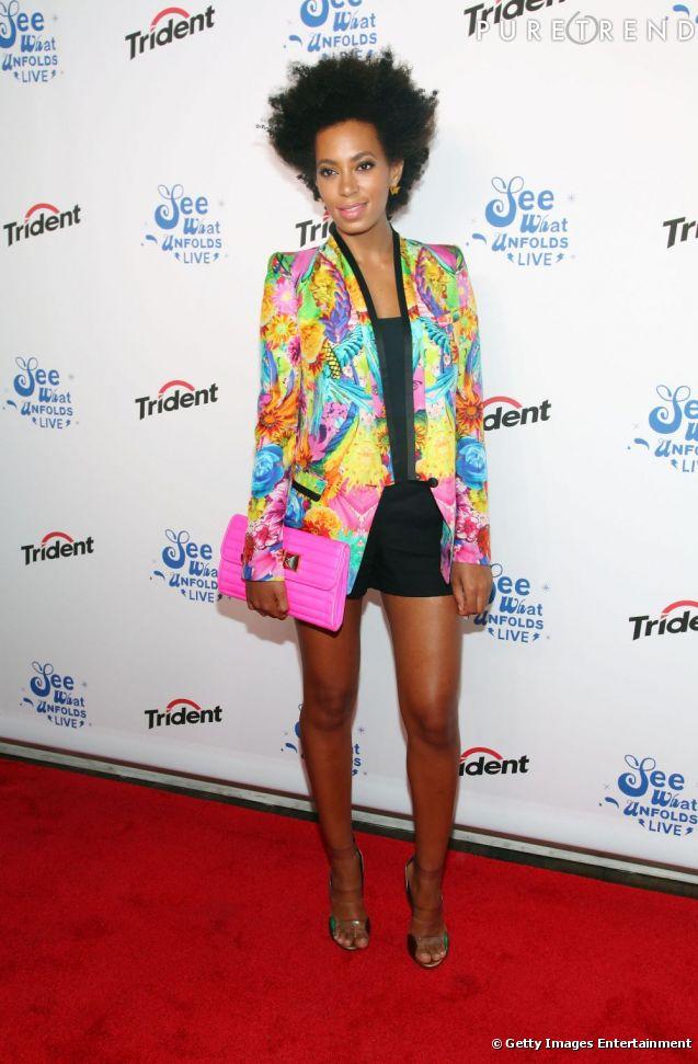 Solange Knowles conclut sa tenue à l'aide d'une pochette fuchsia furieusement mode.