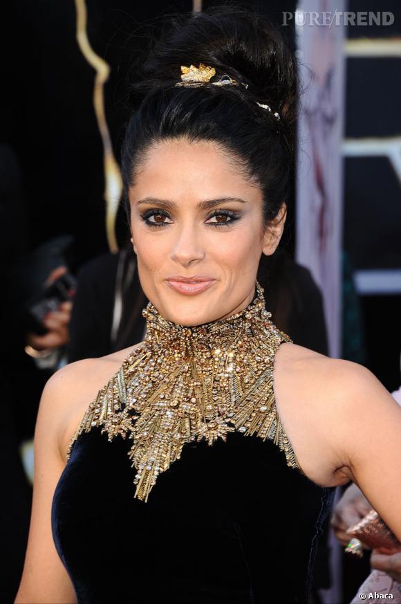 L'Oscar 2013 du beauty look impérial : Salma Hayek.  Avec son chignon boule habillé d'un hairband gold et son smoky black parsemé de fard or, l'actrice se fait Cléopâtre.