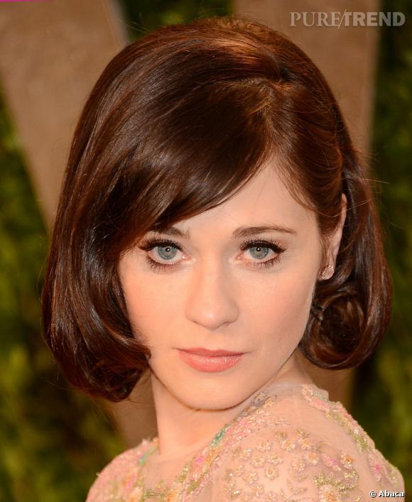 """L'Oscar 2013 du meilleur beauty look preppy :  Zooey Deschanel. L'actrice de """"New Girl"""" est tout simplement adorable avec cette mise en beauté. On aime l'idée du faux carré, de la mèche et du regard rétro."""