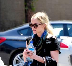 Ashlee Simpson morose dans une tenue qui fait overdose de noir et dont les Dr Martens tassent la silhouette.