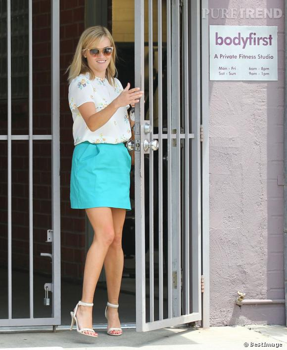 Reese Witherspoon porte un top à fleurs Band of Outsiders avec une jupe turquoise.