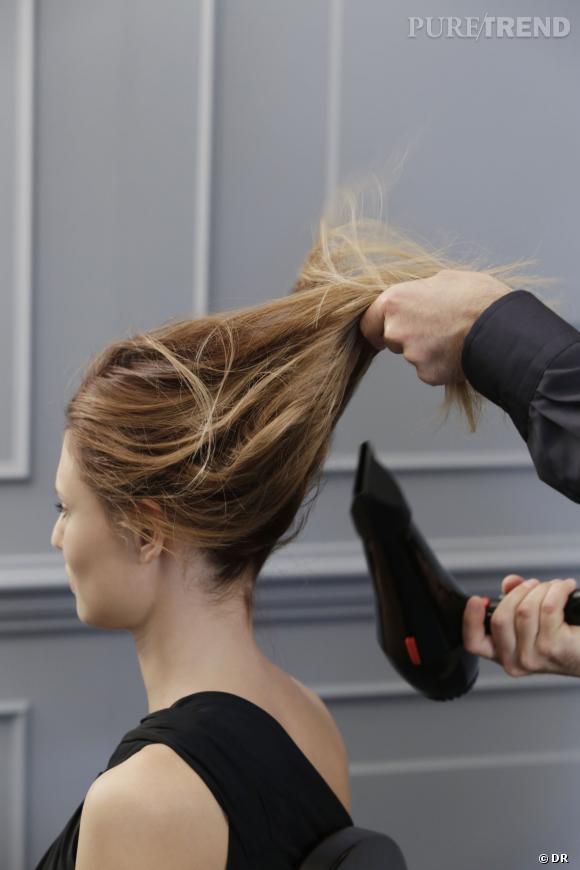 Etape 1 : tirer les cheveux en arrière en soufflant un peu d'air chaud dessus pour qu'ils prennent le pli.