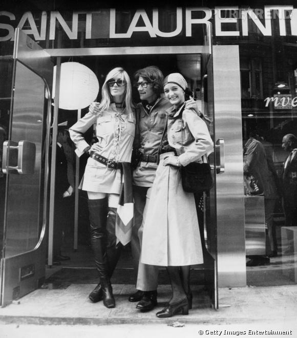 L'équipe de choc. Yves Saint Laurent, prend la pose en 1969 avec Betty et Loulou. Ils sont tous trois vétus de sahariennes, créations d'Yves.