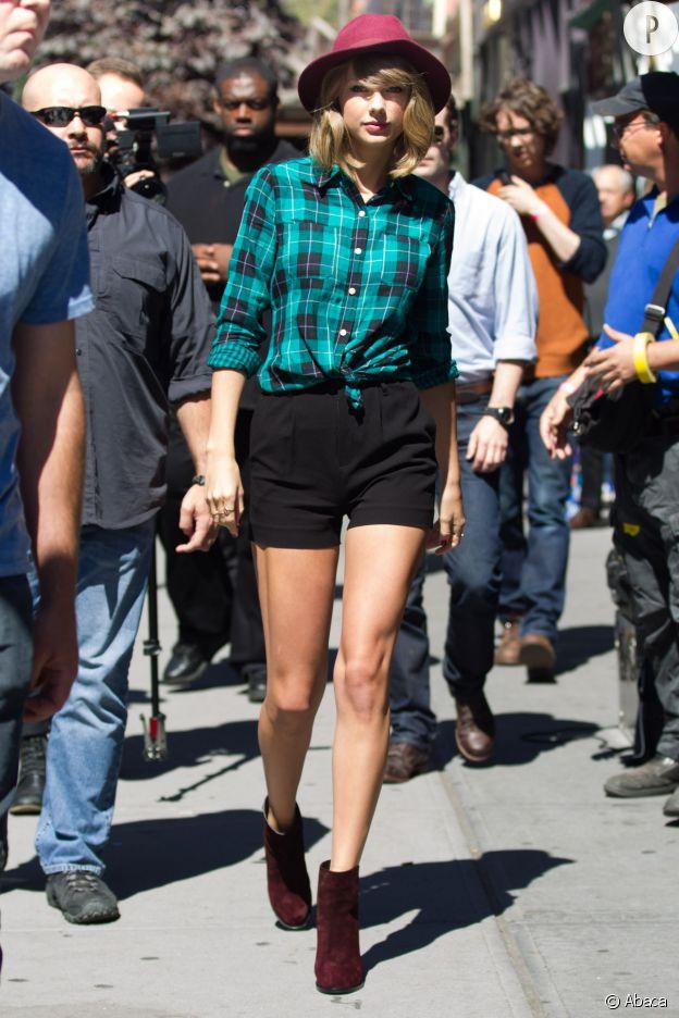 Taylor Swift porte une chemise Junior, un short Alice + Olivia, des bottines Rag & Bone et un chapeau Reiss.