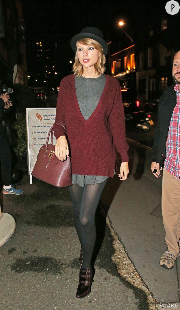 Taylor Swift porte une robe Free People, un pull 525 America, un sac Aldo, des bottines Jimmy Choo et un chapeau Urban Outfitters.