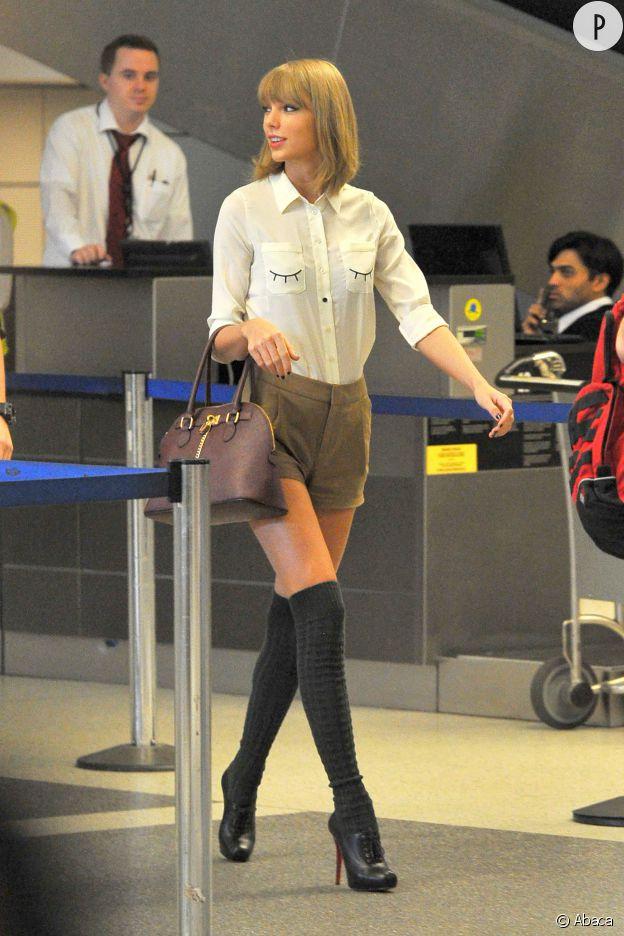 Taylor Swift porte une chemise Miss Patina, un short The Pleated Short, un sac Aldo et des bottines christian Louboutin.