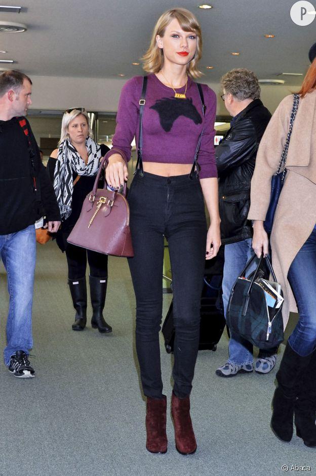 Taylor Swift porte un sac Aldo, un jean Urban Outfitters, un pull Aritzia et des bottines Rag & Bone.