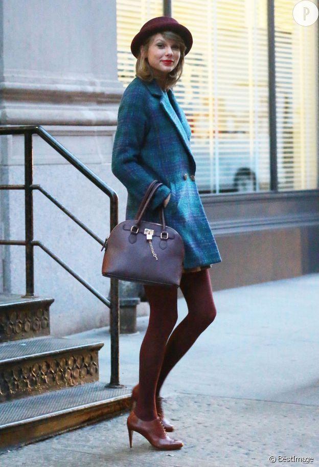 Taylor Swift porte un manteau Miss Patina, un sac Aldo, des Richelieu Cole Haan et un chapeau Free People.