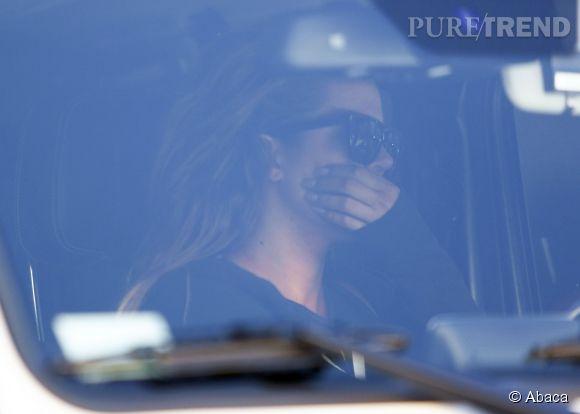 Khloe Kardashian prend soin de cacher sa bouche avec sa main.