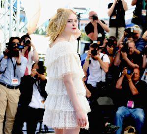Elle Fanning porte une robe blanche à volants.