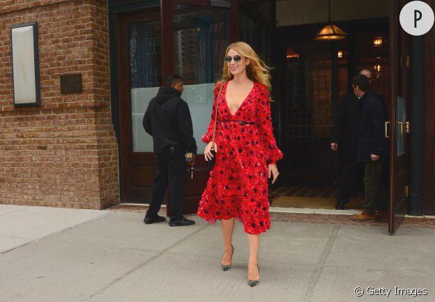 Blake Lively porte une robe rouge imprimée et décolletée.