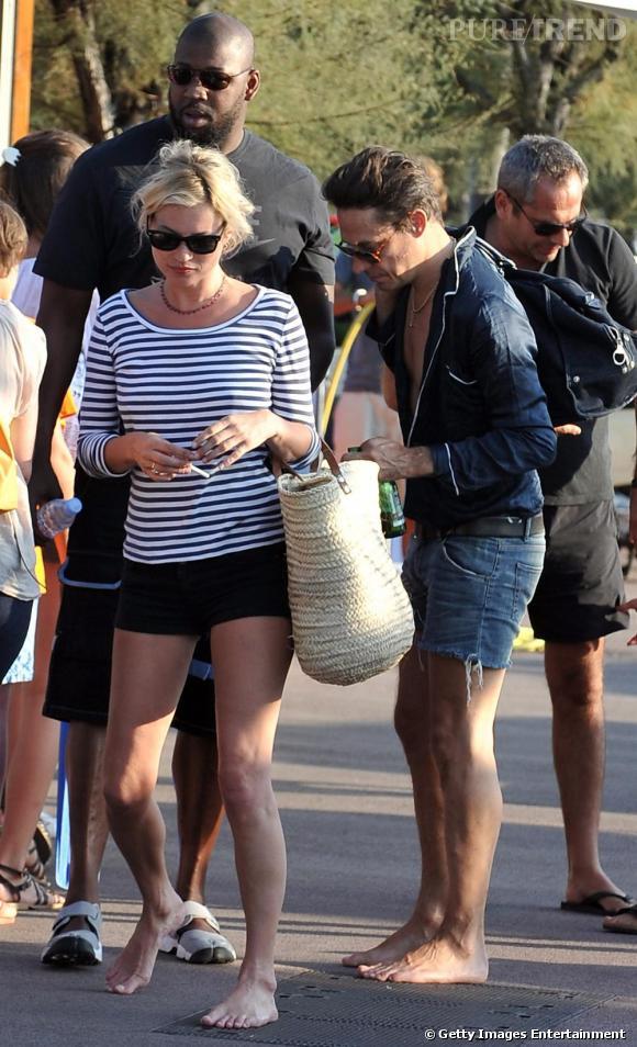 Un look décontracté pour une promenade pieds nus en bord de mer. Marinière, mini short noir, Wayfarer de  [brand=4294959755] Ray Ban [/brand]  et cabas en osier : il suffit d'un rien à Kate Moss pour être tendance.
