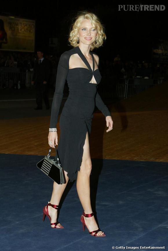 Naomi Watts dans une robe noire ultra moulante très nude : décolleté glamour et fente à la cuisse, + escarpin rouge en satin.