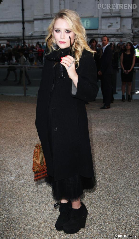 Mary Kate Olsen joue les dames en noir en total look Burberry. Manteau d'homme robe longue et boots compensées : un look pointu qui ne passe pas inaperçu.