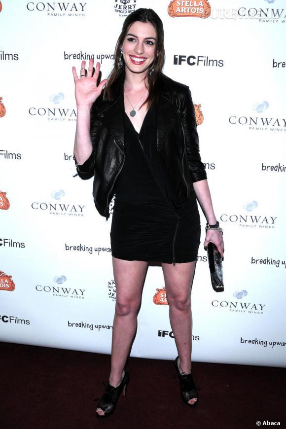 Anne Hathaway opte pour une allure rock et sexy avec un perfecto en cuir et une petite robe noire moulante.