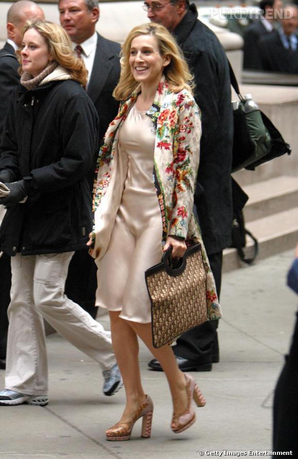 Toujours très preppy, Carrie Bradshaw surfe à nouveau sur la tendance lingerie avec une robe en satin mais reste fidèle à elle même en mixant sans états-d'âme imprimés floraux et logo Dior.