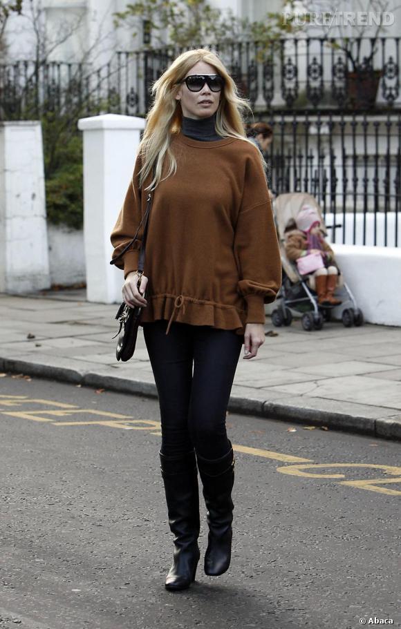 Bottes noires, jean slim brut et pull cocoon, Claudia Schiffer s'offre une allure urbaine et féminine. Le bémol ? Les lunettes masque peu chic et le col roulé gris, un peu démodé associé au marron.