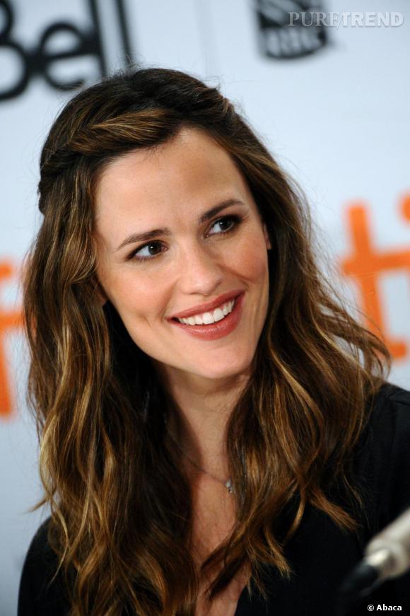 Cheveux ondulés, l'actrice agrémente sa coiffure de fines tresses formant une sorte de couronne.
