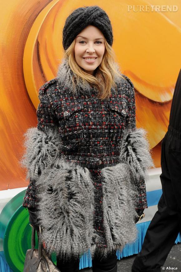 Kylie Minogue s'emmitoufle dans un manteau en tweed Chanel.