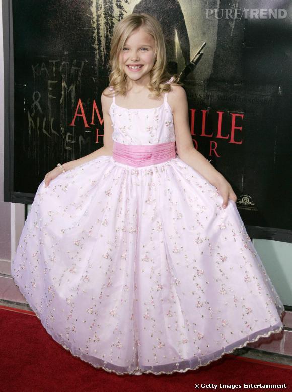 Chloë Moretz, 8 ans, fait la révérence devant l'affiche d'Amityville, son premier rôle à succès au cinéma.