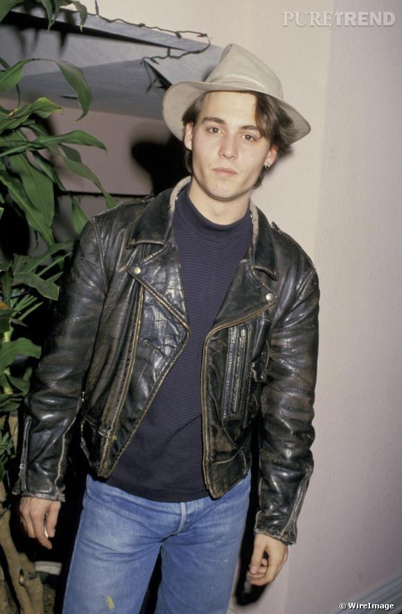 En 1987, Johnny est un petit nouveau du red carpet. Certains de ses basiques sont cependant déjà présents dans son look comme le perfecto, la boucle d'oreille et un chapeau.