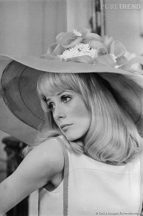Une Deneuve candide avec sa frange et sa capeline, beauté incontournable des années 60.
