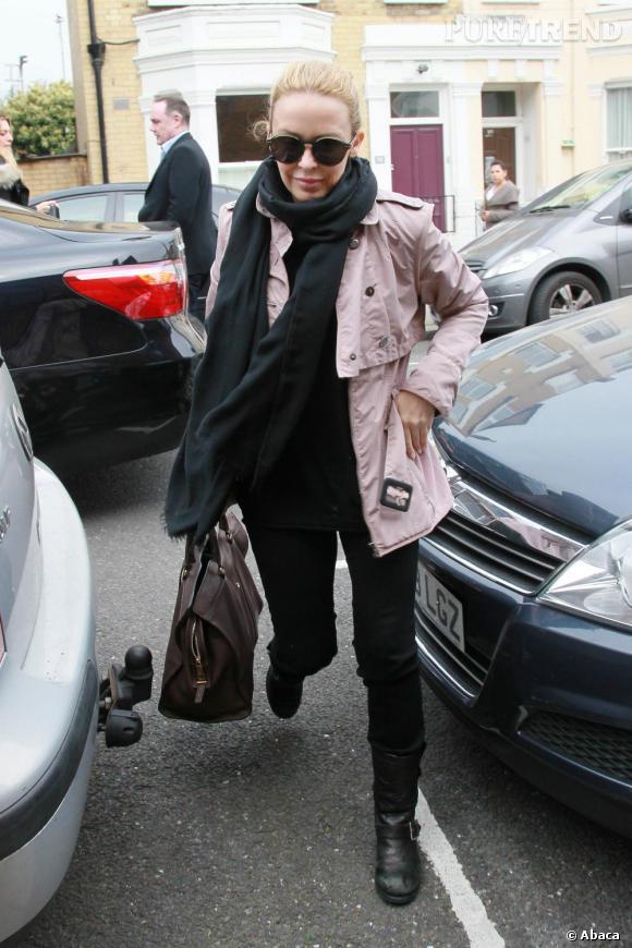 Pantalon droit noir, boots de biker et lunettes rondes, Kylie Minogue parie sur des détails rock et rétro qu'elle réhausse avec un trench court rose poudré.