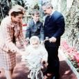 La princesse Grace dans un look en tweed en 1964 au côté de son mari et de ses deux enfants : Stephanie sur un vélo et Albert derrière.