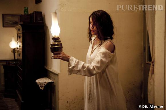 L'actrice porte des habits d'époque pour coller à son personnage. Ici, une robe de chambre longue, en coton blanc.