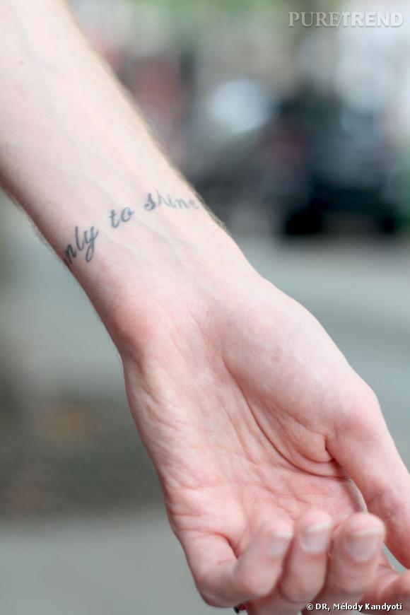 Les lettrages sur son poignet font écho à ceux tatoués sur son torse.