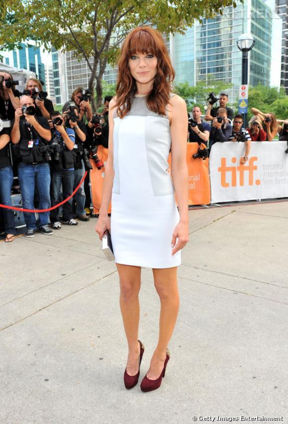 """Emma Stone fait dans le minimalisme, avec une robe blanche """"trois trous"""" Calvin Klein Collection, qu'elle booste avec des escarpins bordeaux."""