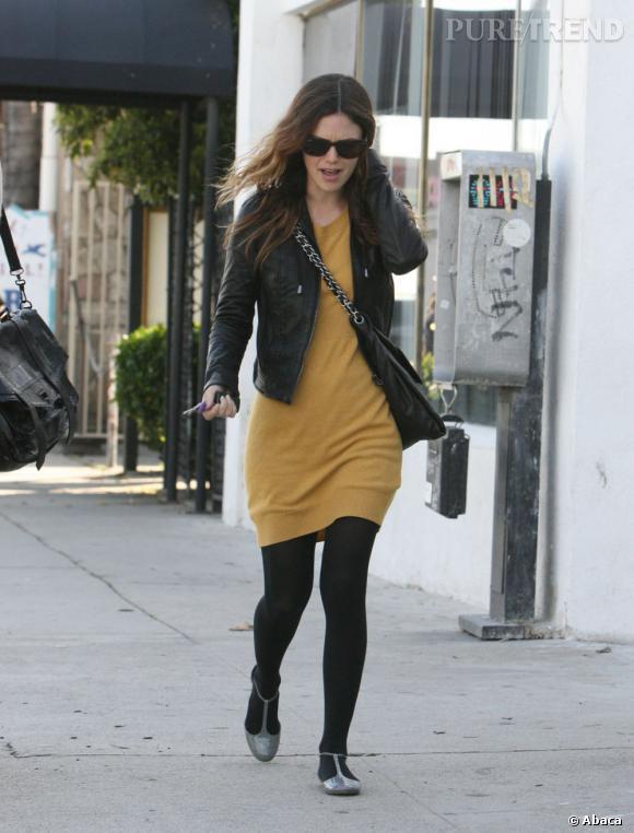 Rachel se rattrape ici avec une robe-pull en maille moutarde. On note une fois de plus que l'association avec du noir et toujours réussie.