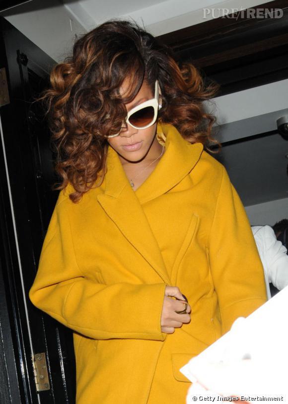 Rihanna, emmitouflée dans une veste en laine moutarde. Elle insiste sur le côté 70's avec les grosses lunettes mouche à montures blanches.