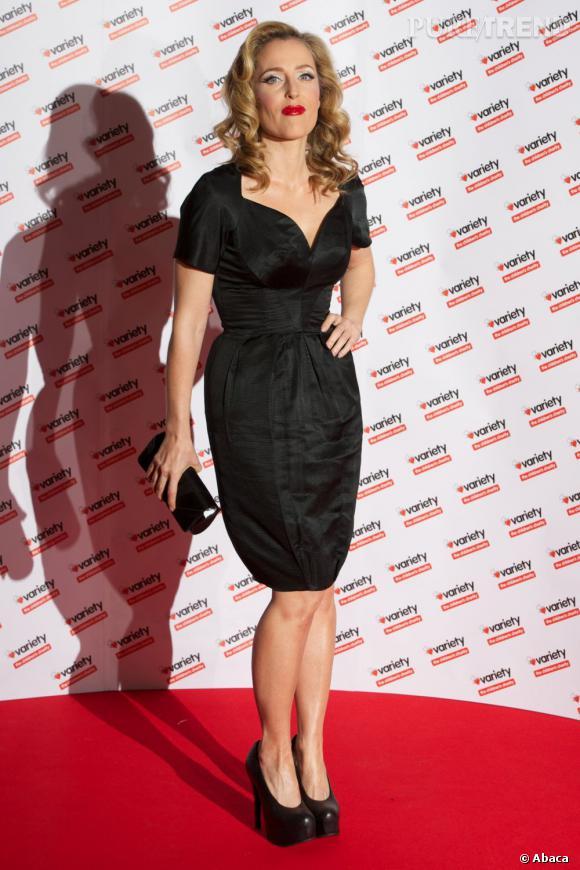 L'actrice porte une robe vintage Estevez noire qui flatte sa silhouette.