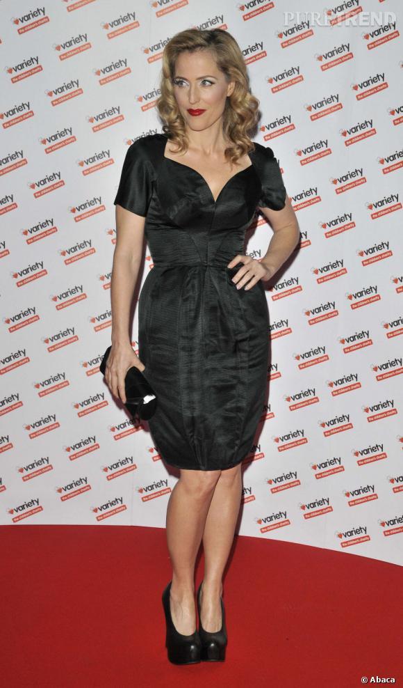 Gillian Anderson se juche sur des escarpins ultra-plateformes noirs pour allonger sa silhouette.