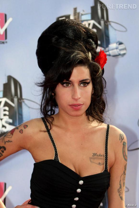 Amy Winehouse agrementait très souvent sa chevelure d'accessoire. Ici, la fleur rouge contraste avec sa couleur foncée.