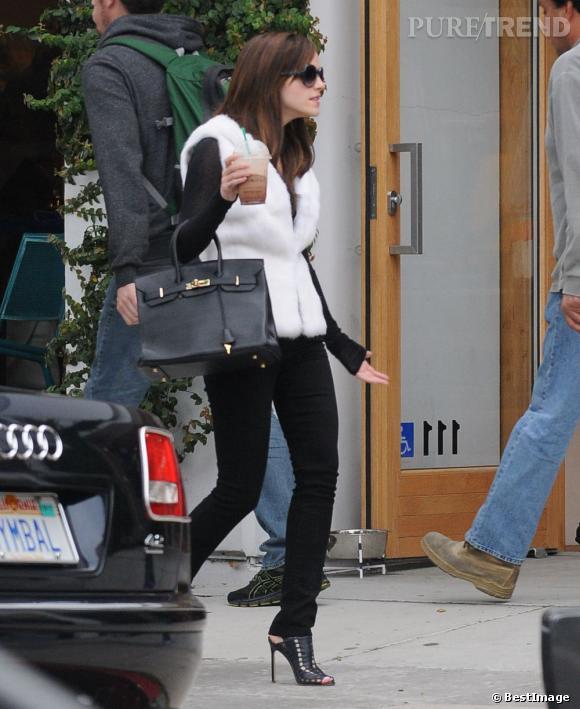Emma Watson se juche sur des sandales noires pour allonger sa silhouette.