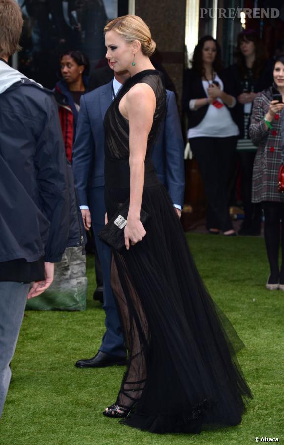 Charlize Theron se juche sur des sandales plateformes noires.