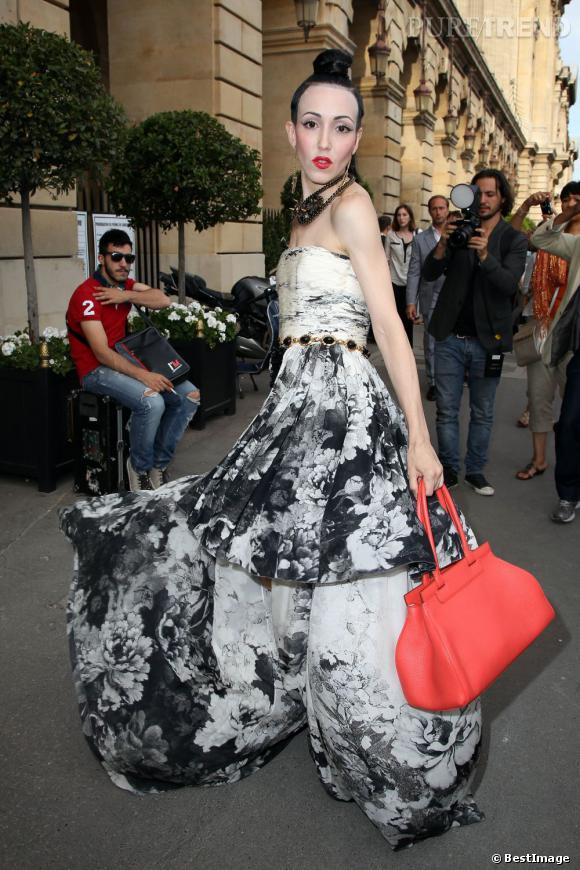 Elle choisit une robe très show off avec un jeu de longueur et complète le tout par des bijoux très bling-bling et un sac Moynat Pauline corail.