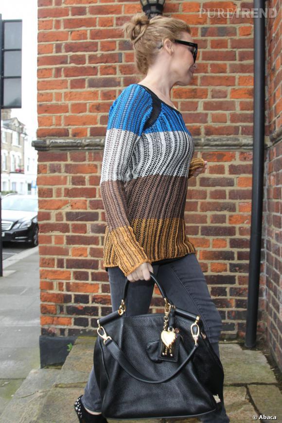 Elle complète sa tenue avec un sac noir et détails dorés.