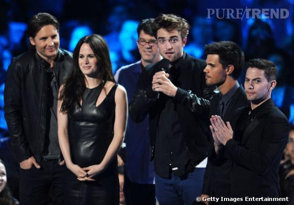 Robert Pattinson aux VMAs, bien entouré et souriant.