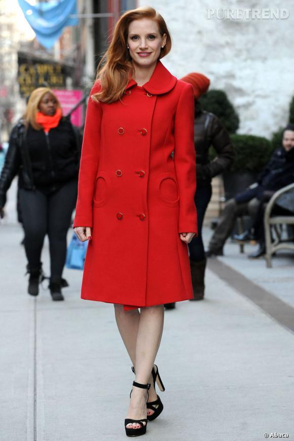 Jessica Chastian réchauffe ses jambes nues avec un manteau rouge.